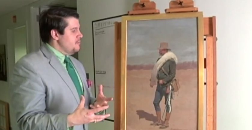Birmingham Museum of Art chief curator stands with the 1896 Remington painting (Photo captured from WIAT's report)