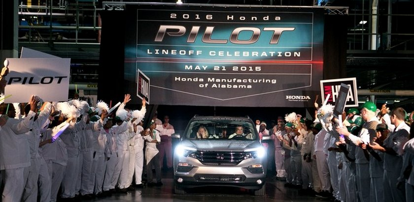 Employees celebrate as the first new Honda Pilot is rolled off the line