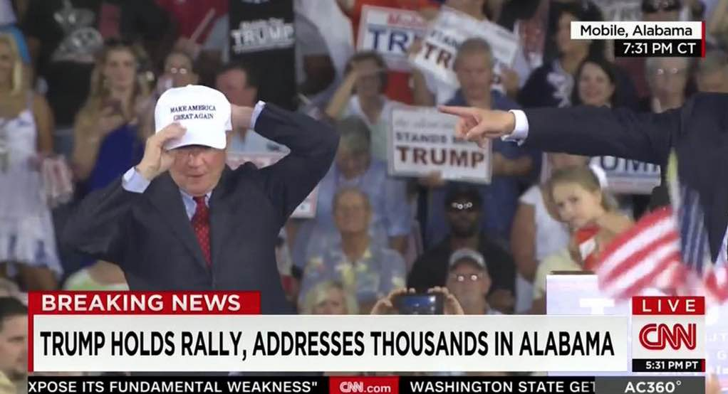 "Senator Jeff Sessions dons a ""Make America Great Again"" hat at Donald Trump's Mobile rally."