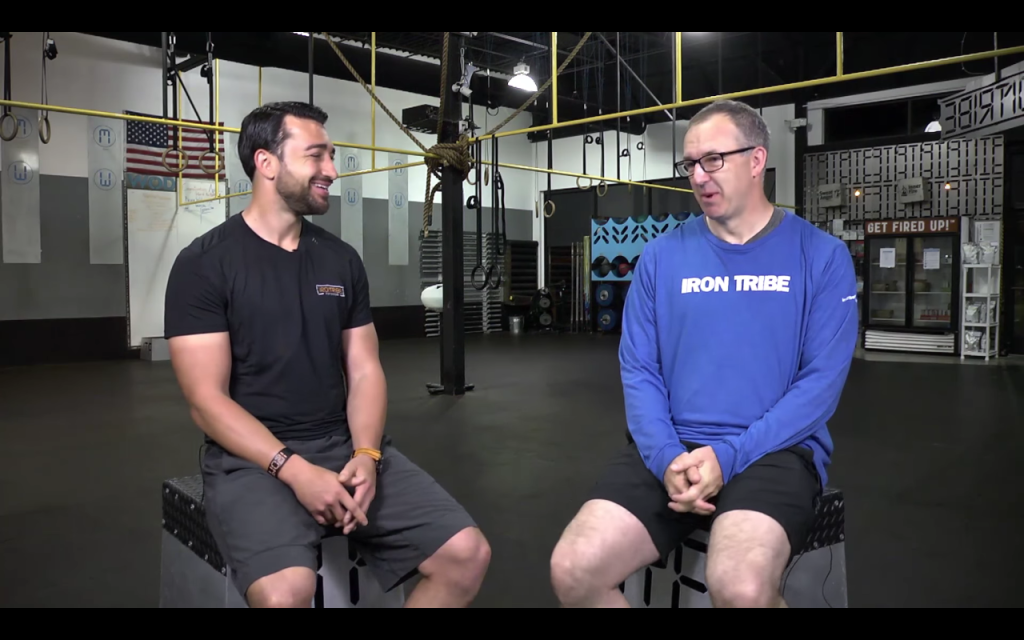 SEC Commissioner Greg Sankey talks with Iron Tribe Fitness President Jim Cavale during a testimonial. (Photo: Screenshot from Iron Tribe Fitness video)