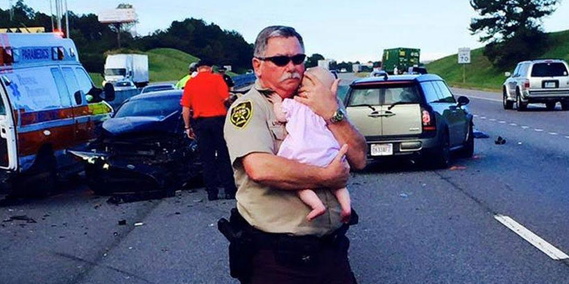 Deputy comforts baby at the scene of an Alabama vehicle  wreck