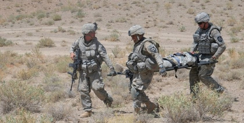 Infantry Soldiers from 4th Battalion, 23rd Infantry Regiment, 5th Stryker Brigade Combat Team carry a wounded Stryker Soldier on a litter to be medically evacuated (MEDEVAC) after rolling over an anti-tank mine in Zabul Province, Afghanistan. (Brian Naranjo)