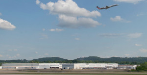 The Kaiser Aircraft facility stands in the background as a jetliner takes off at Birmingham-Shuttlesworth International Airport. (Image: Bob Farley/F8Photo.org)
