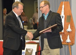 NASA's Tim Lawrence presents Southern Research's John Koenig with an honorary award for his contributions to space flight.