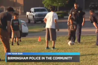 Birmingham police officers play soccer with a group of kids
