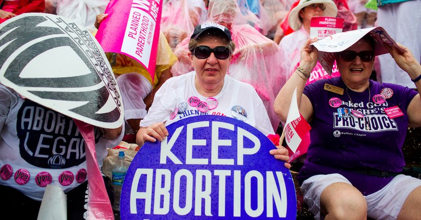 Women attendants of a Planned Parenthood rally try to keep dry after a sudden storm moved through the Tampa area on August 29.   (Photo: Mallory Benedict/PBS NewsHour)