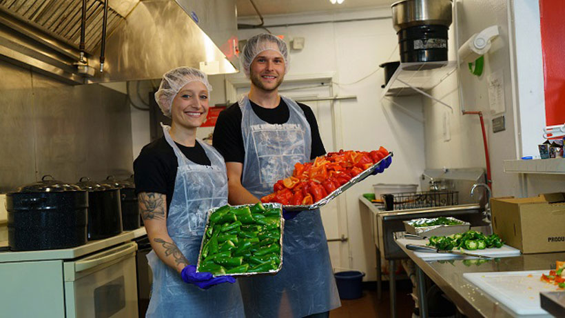 Allie Clark and Colin Woltmann, a.k.a. The Hummus People, hold some of the fresh ingredients they put into their increasingly popular products. (Mark Sandlin/Alabama NewsCenter)