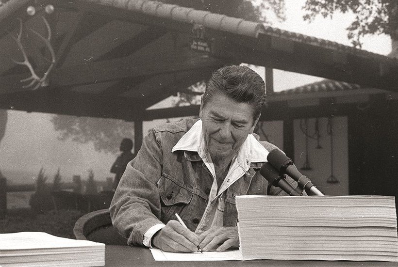 President Ronald Reagan signs the largest tax cut bill in U.S. history at his ranch in California, with the porch and fencing that he built in the background.